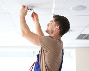 smoke detector being installed by young man onto the ceiling