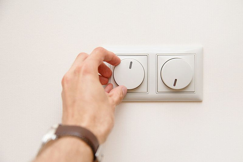 Human hand turning down electrical light dimmer switch to dim the lights and conserve energy