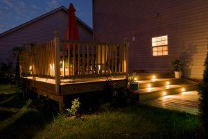 Lit up deck at night from lights in stairs and along the railing