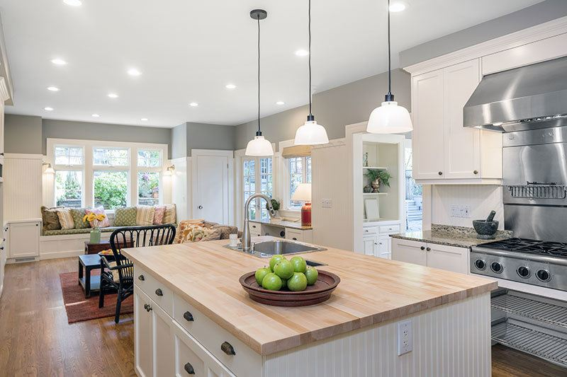 Bright kitchen with recessed lighting, pendant lighting over an island, and task lighting over stove top
